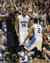 Duke University's Hariston and Cook react during the second half of their NCAA basketball game against the University of Maryland as Maryland's Cleare looks on in Durham