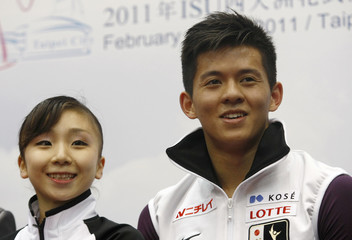 Narumi Takahashi and Mervin Tran of Japan smile to cameras after performing during the pairs free skating program competition at the ISU Four Continents Figure Skating Championships in Taipei