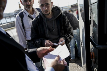 Migrants display their tickets to a travel agency employee before boarding a bus heading to the borders of Greece with Macedonia, following their arrival on the Blue Star Patmos passenger ship at the port of Piraeus