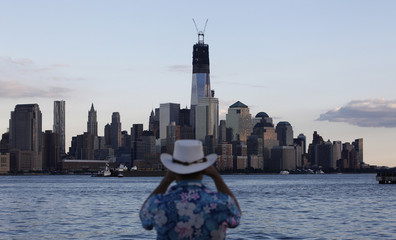 One World Trade Center stands tall on the skyline of New York's Lower Manhattan as a man takes a picture from a pier in Hoboken, New Jersey