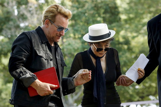 Artist Yoko Ono, the widow of John Lennon, is helped by Irish singer Bono after her remarks during the unveiling of a tapestry honoring Lennon at Ellis Island in New York