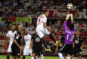Sevilla's Martin Caceres heads the ball next to Deportivo Coruna's goalkeeper Manuel Fernandez in Seville
