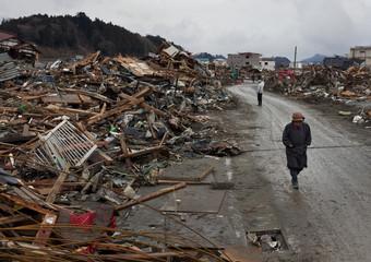 A woman walks past debris in Rikuzentakata