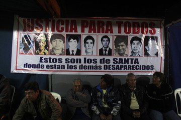 People sit near a poster with photos of the nine farmers killed by the Grupo Colina death squad in 1992, in the village of Santa