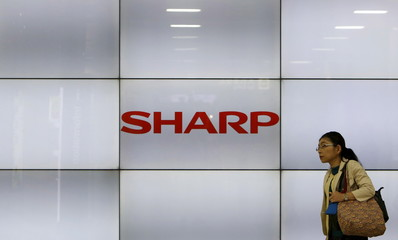 A woman walks past display showing a logo of Sharp Corp in Tokyo