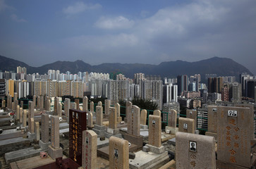Gravestones are seen with high rise residential blocks in the background in Hong Kong