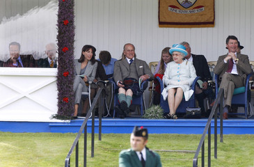 Britain's Prime Minister Cameron sits during the Braemar Royal Highland Gathering in Scotland