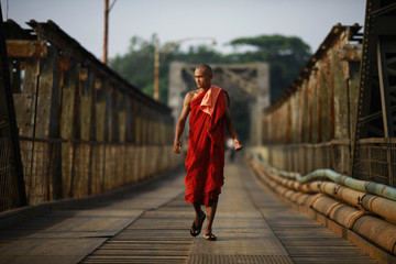 A Buddhist monk walks across an iron bridge built during the country's colonial period, over the Ngamoeyeik creek in Yangon