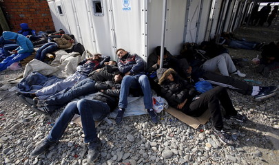 Migrants wait for transport to Serbia at a transit camp after entering the country by crossing the border with Greece in Gevgelija