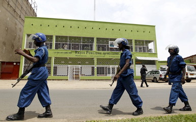 Riot policemen walk outside the Radio Publique Africaine broadcasting studio in the capital Bujumbura,