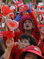"""A member of the pro-government """"red shirt"""" group use a noisemaker during a rally in Nakhon Pathom province"""