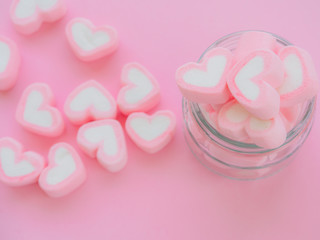 Closeup of sweet marshmallow in the shape of heart in jar on pink background. Concept about love and relationship. (Soft Style for Background)