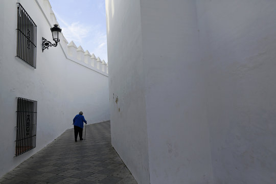 A woman walks aided by a cane on International Day of Older Persons in Tomares, near the Andalusian capital of Seville