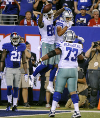 Cowboys wide receiver Kevin Ogletree celebrates his second touchdown of the game with teammates Miles Austin and Mackenzy Bernadeau during their NFL football game in East Rutherford