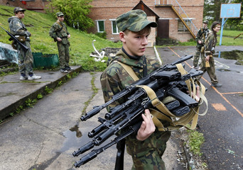 A student of the Scorpion Youth Military Club carries AK-74 Kalashnikov automatic rifles for a training session on a summer base in a school in Molodyozhny