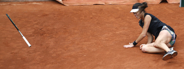 Ana Ivanovic of Serbia falls on the court during the women's singles match against Ekaterina Makarova of Russia at the French Open tennis tournament at the Roland Garros stadium in Paris