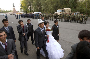 A newly wed couple walks, with Interior Ministry officers and servicemen lining up in the background, on a street in the city of Osh