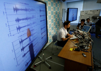 Japan Meteorological Agency's earthquake and tsunami observations division director Gen Aoki speaks next to graphs of ground motion waveform data observed in Japan during a news conference at the Japan Meteorological Agency in Tokyo