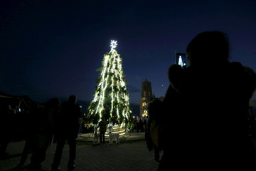 People take pictures during a celebration of the lighting of a 12-metre-tall Christmas tree at a Lutheran Church, which stands on a baptism site on the Jordan River, in Shouneh