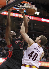 Toronto Raptors' Gay dunks over Cleveland Cavaliers' Zeller during their NBA basketball game in Cleveland