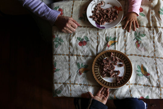 Asun Querol Revilla feeds lunch to her grandchildren Sheila and Andres before learning that their eviction by the Municipal Housing and Land Company was suspended in Madrid