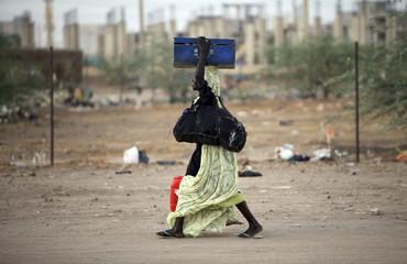 A labourer carries her belongings as she walks home after work in Khartoum