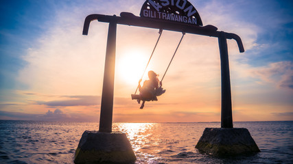 Girl on a swing in the sea during sunset on Gili Island, Lombok, Indonesia