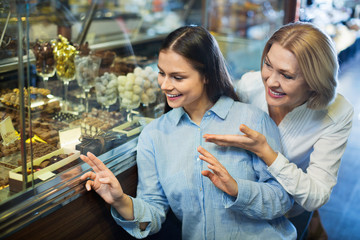 Cheerful female friends selecting fine chocolates and confectionery