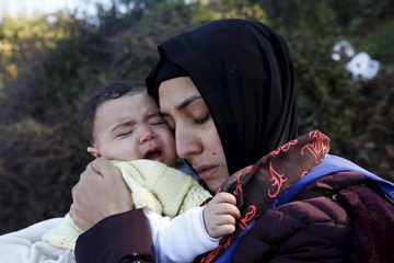 A Syrian refugee hugs her crying baby after arriving on a raft on the Greek island of Lesbos