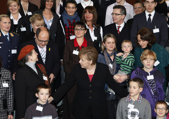 German Chancellor Merkel poses for pictures with relatives of German soldiers and police staff who serve on missions abroad at Chancellery in Berlin