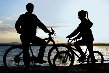 Image of sporty family on bicycles outdoors against sunset. Silhouette