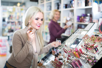 Young woman choosing face powder .