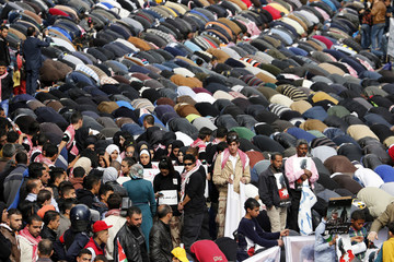 Muslims perform Friday prayers along a street outside al-Husainy mosque before a march in downtown Amman