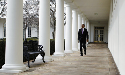 U.S. President Obama walks alone on the Colonnade at the White House in Washington