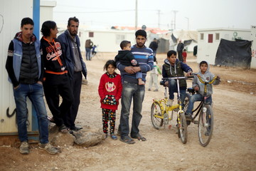 Syrian refugees look at the convoy of U.N. High Commissioner for Refugees in Al-Zaatari