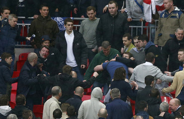 Millwall fans fight during FA Cup semi-final soccer match against Wigan Athletic at Wembley Stadium in London