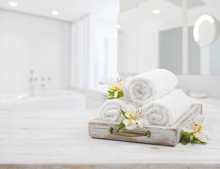 Vintage drawer, spa towels and orchid flowers over blurred bathroom