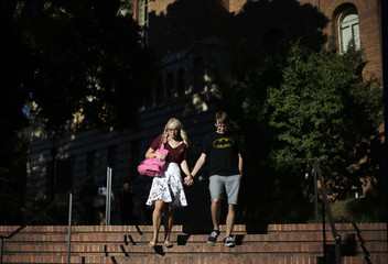 Couple holds hands as they walk on campus as new UCLA students move into campus residence halls in preparation for the new school year, in Los Angeles