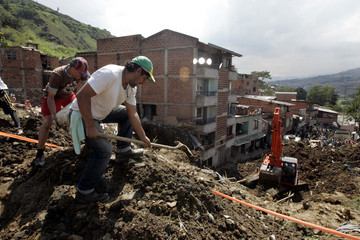 Residents dig at the site of a landslide in Bello