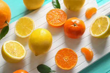 White cutting board with different citrus fruits on blue wooden background