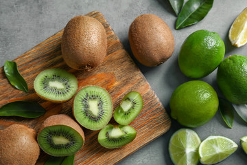 Wooden cutting board with fresh lime and kiwi fruits on grunge background