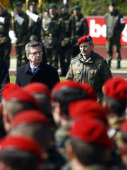 German Defence Minister de Maiziere walks past German Bundeswehr army soldiers of the ISAF during a welcome ceremony in Amberg