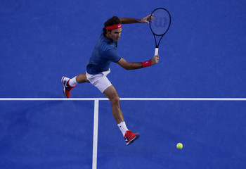 Roger Federer of Switzerland hits a return to Andy Murray of Britain during their men's singles quarter-final tennis match at the Australian Open 2014 tennis tournament in Melbourne