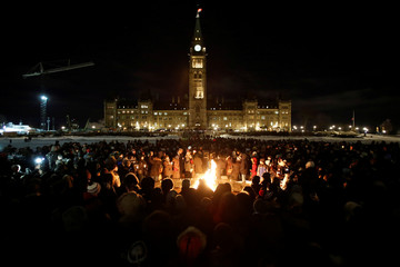 People gather around the Centennial Flame on Parliament Hill during a vigil following a deadly shooting at a Quebec City mosque, in Ottawa