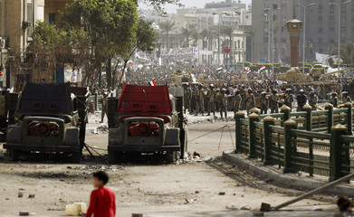 The Egyptian army stands guard near burnt vehicles at Tahrir Square in Cairo