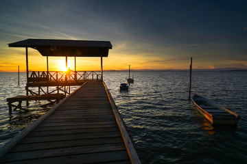 Serene sunrise beach over fishing jetty with fishing boats in Tanjung Aru village,Labuan island,Malaysia.