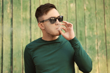 Handsome young man smoking weed near wooden fence outdoors