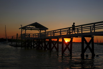 A woman is seen silhouetted while walking a dog at sunset on Manhasset Bay in Port Washington, New York