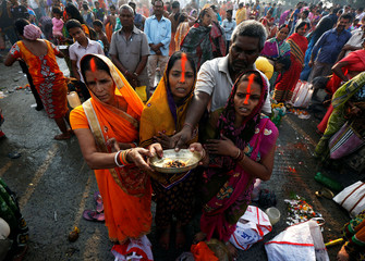 Hindu women worship after taking a holy dip in the Ganga river on the occasion of the annual Hindu festival of 'Karthik Purnima' or full moon night, in Kolkata