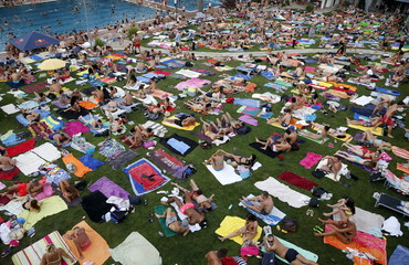 People relax at the public swimming pool of Schoenbrunner Bad in Vienna